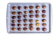 Whole roasted chestnuts on a roasting tray Stock Photos