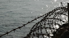 Barbed Wire - Borders, frontiers by the sea. - stock footage