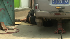 Chinese car repair, migrant workers, Beijing - stock footage