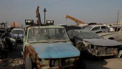 Cars On Scrap Yard. A worker actioning a chain lever Stock Footage