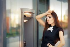 Stressed Woman with credit card at ATM - stock photo