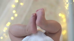 Legs newborn on a background of bokeh lights Stock Footage