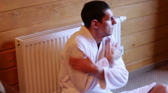 Man freezes near the radiator in the house - stock footage