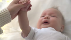 The mother and the newborn baby holds the hand when the child cries. From hand Stock Footage