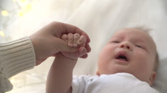 The mother and the newborn baby holds the hand when the child cries. From hand - stock footage