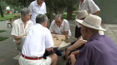 Old men playing Chinese checkers in park - stock footage