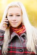 Young blonde talks on cellular telephone Stock Photos