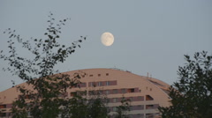 Moon over roof of building Stock Footage