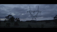 High voltage power lines across a country lanscape at dusk Stock Footage