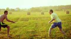 Young friends play the fool in the field during sunset with wooden rapier in Stock Footage
