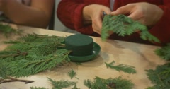Stock Video Footage of People Cut Green Branches and Add it to Wreath People Are Making A Christmas