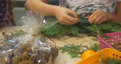 Stock Video Footage of Girl Gathering a Branches to Create a Wreath People Are Making A Christmas