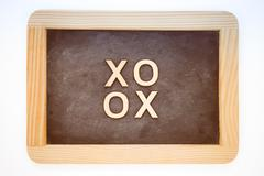 Wooden frame vintage chalkboard isolated on white with text XOXO (kisses &amp Stock Photos