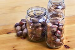 Nuts on glass jars over wooden surface Stock Photos