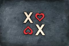 Vintage chalkboard with text XOXO (kisses & hugs) created of wood letters - stock photo