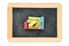 Wooden frame vintage chalkboard isolated on white with colored chalk pieces Stock Photos