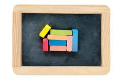 Wooden frame vintage chalkboard isolated on white with colored chalk pieces - stock photo
