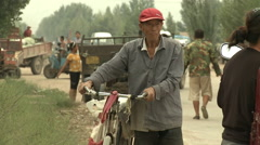 Old Mongol man wheeling bike, China Stock Footage