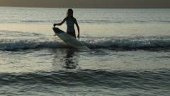 A girl practicing surfing in shallow water at a beach in Playa Venao, Panama Stock Footage