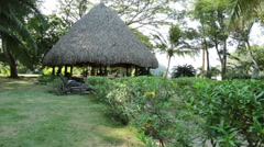 A thatch roof next to a beach in Playa Venao, Panama with chairs under it Stock Footage