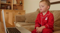 A little boy in Christmas pajamas watches show on computer Stock Footage