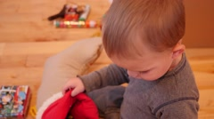 Cute little boy looking through his Christmas stocking - stock footage