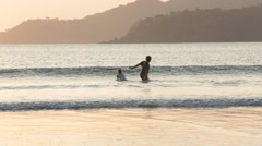 Two children playing in the waves on the beach of Playa Venao, Panama - stock footage