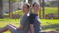 Identical twins sitting in a park, smiling Stock Footage