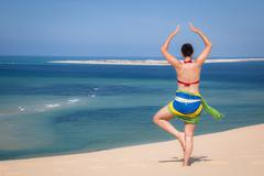 Girl in a standing yoga pose in the beach Stock Photos