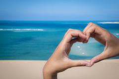 Hands making a heart sign at the beach Stock Photos