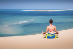 Girl in a sitting yoga pose in the beach Stock Photos