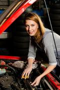 Young female trainee fixing car engine in garage Stock Photos