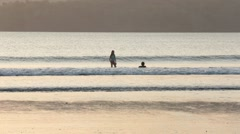 Children playing in the waves on a beach - stock footage