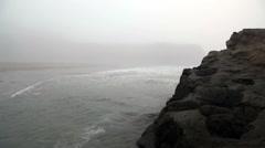 Gentle Ocean Waves Around Large Rock Shrouded In Fog Stock Footage