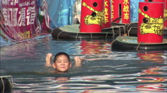 Young Chinese boy swimming & smiling, China Stock Footage