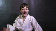 Karate boy angry kid shouts waving his arms defeat Stock Footage