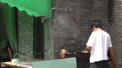 Chinese man cooking kebabs on grill, Beijing Stock Footage