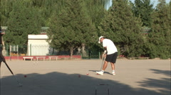Chinese man playing croquet in Beijing park - stock footage