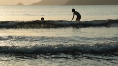Silhouettes of two people in the water on a beach in Playa Venao, Panama Stock Footage