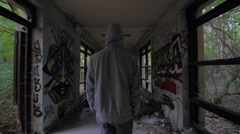 Slow motion of a guy with hood walking through abandoned building Stock Footage