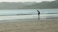 Young man skim boarding on the shore of a tropical beach Stock Footage