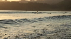Wave rolling into a beach with people surfing in  Playa Venao, Panama Stock Footage