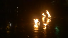 Burning Torches Are Lying on a Paved Square After Performance of Dance Troupe Stock Footage