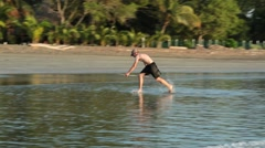 Teenager trying to skim board on the shore of a tropical beach Stock Footage