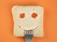 Happy toast with a fork in her mouth - stock photo