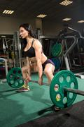 Brunette strong fitness sexy woman doing barbell squats in a gym Kuvituskuvat