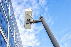 Spy on pole near modern building in blue sky Kuvituskuvat