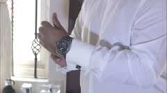 Stock Video Footage of man in white wedding shirt clasps watches on hand