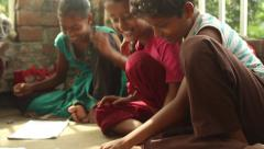 Simple, sweet Indian boys and girls laugh and draw happily with each other Stock Footage