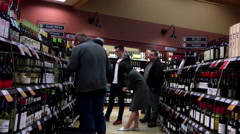 People choosing wine inside BC liquor store on Christmas eve date - stock footage